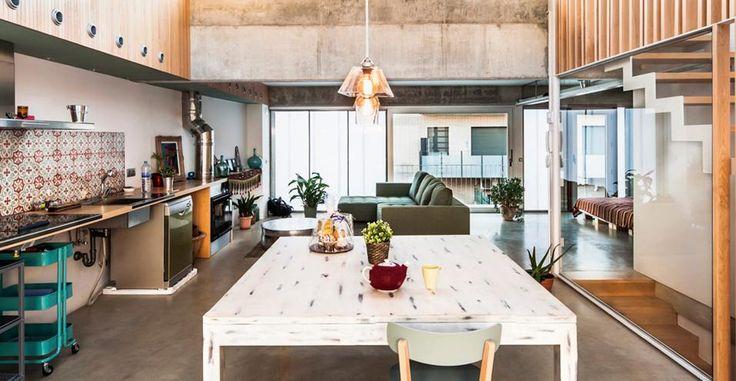 Open space in stile catalano. Una zona giorno ricca di contrasti. Gli architetti hanno mixato con equilibrio arredi vintage e pezzi custom-made, sperimentando l'uso di materiali diversi a confronto, come cemento, legno naturale e ceramica decorata.