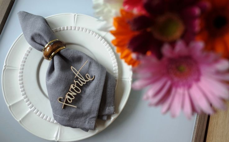 White plates with decor. Gerberas, gray napkin and napkin rings.