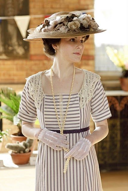 This is an Edwardian costume from Downton Abbey. It's a classy look as it shows off the chest, which is draped with pearls, but doesn't show any clevage. The lace detailing on the simple striped dress makes it really elegant. Teamed with the floral hat and cute gloves, which I wish we still wore today because they are just so elegant, makes such a clean classic look.
