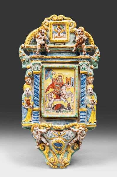 ACQUASANTIERA IN MAIOLICA, DERUTA XIX SECOLO interamente a smalti policromi, centrata da dipinto a San Giorgio e il drago. Figure di apostoli e cherubini laterali e nel basso. Misure cm. 45 x 22.