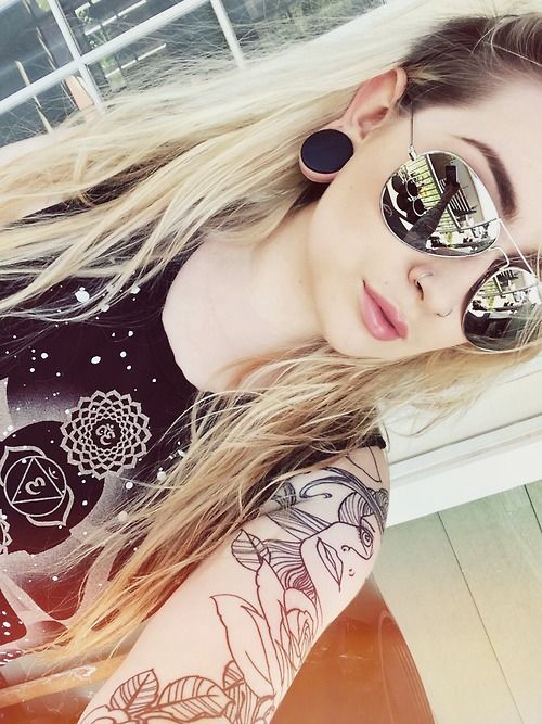 Stretched ear lobes/gauges. Tattooed girl. Shades. Alternative rock chic summer style.