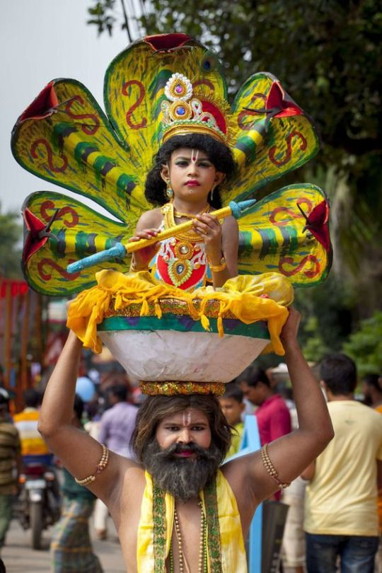 A man with a child dressed as Lord Sri Krishna take part in the celebration of the religious festival Janmashtami, India