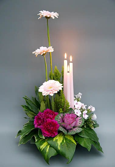The candles add a extra touch to this floral design.