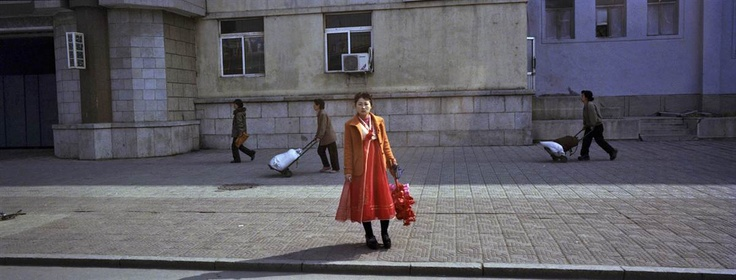 A North Korean woman holding artificial flowers stands on the side of a road in Pyongyang on April 7, 2012, after returning from a rehearsal for a parade to honor North Korean leaders.