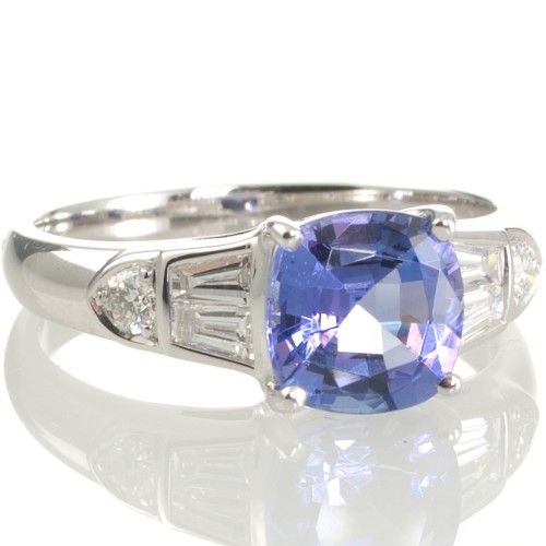 An 18ct white gold ring featuring a 1.67ct cushion cut Tanzanite four claw set between two pairs of tapered baguette cut diamonds. View our collection of antique, Art Deco and modern rings at www.rutherford.com.au