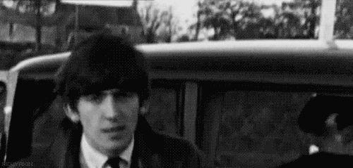 George Harrison, combing his Beatles haircut.