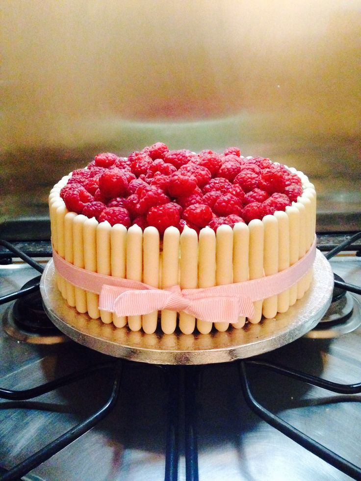 Lemon Sponge Birthday Cake topped with White Chocolate Buttercream Frosting, fresh raspberries and finished with White Chocolate Fingers
