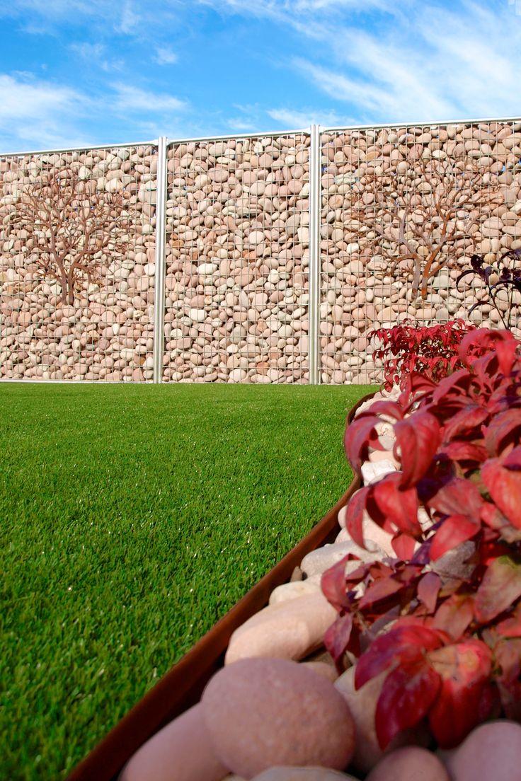 cesped artificial en jardines de diseño. Un gabion con rocas para el muro perimetral y un jardin de cesped artificial con jardinerias delimitadas con bordillos de acero corten y piedras decorativas #cespedartificial