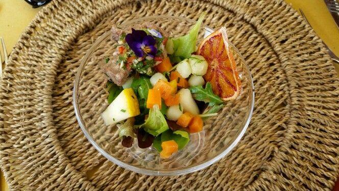Insalata, fiori, agrumi e carne