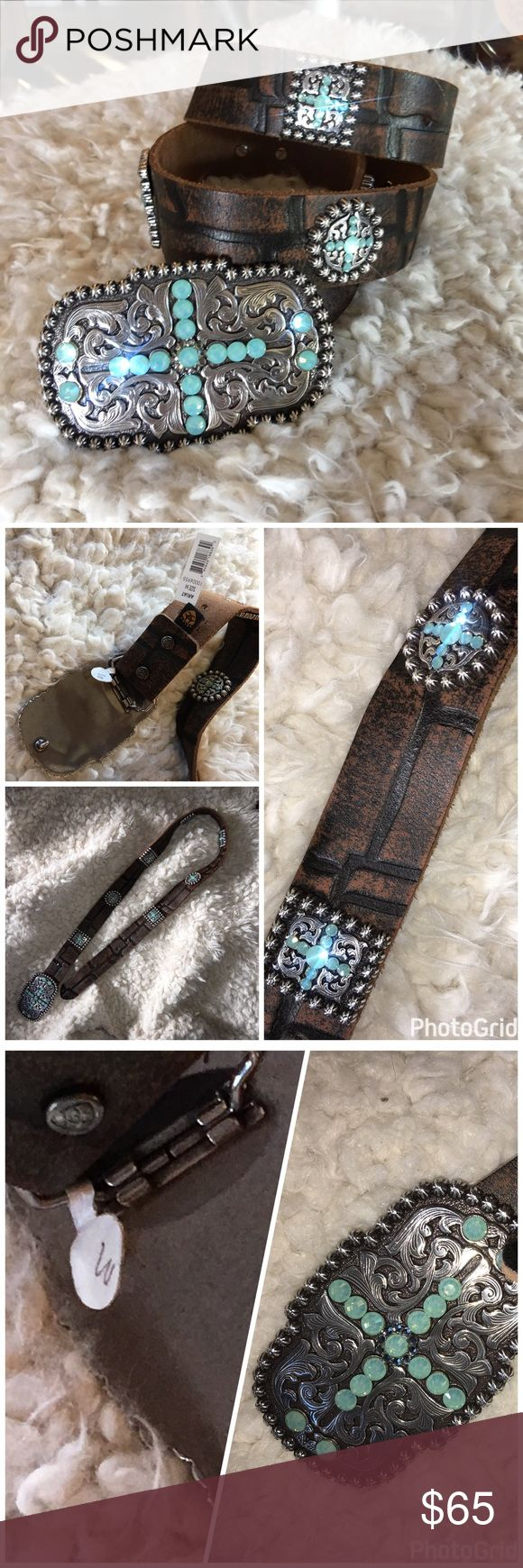 "NWT 🆕 Ariat western Blue Sunday Leather Belt This Ariat western floral design & Swarovski Crystals on the buckle gives you an original cowgirl look. The belt strap has crocodile print & Swarovski Crystals on conchos. The removable buckle lets you customize. Sz= M⭐️Total leather L 39"" x 1.5"" W  Western floral scroll work buckle w/blue Swarovski Crystals in a cross pattern Matching round & square conchos on belt. Distressed croc print leather strap. Has few scratches that are were the wholes…"