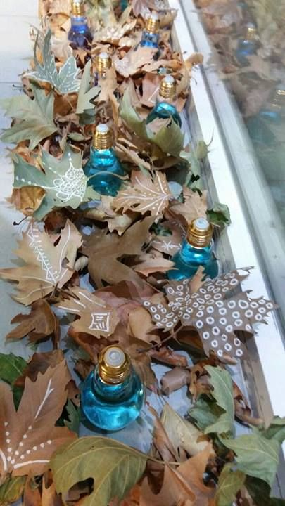 Beautiful detail of autumn shop window in Salamis. The leaves are real and they are painted with chalk paint and the bulbs are filled with light blue water.