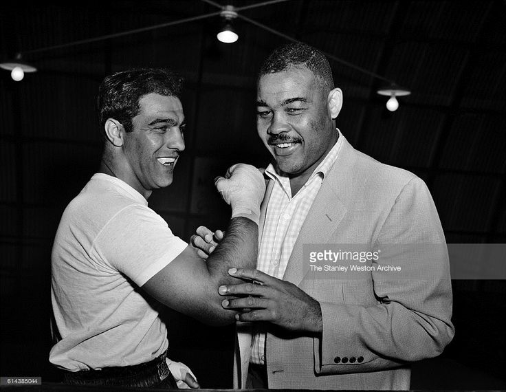 Rocky Marciano and Joe Louis talk boxing where Marciano is training for his title defense against Archie Moore at Grossingers, New York, September 1, 1955.