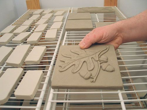 Two tricks (and more) for making perfectly flat tiles: (1) Roll them out on drywall and do NOT move them until they're quite dry; (2) when they're no longer malleable, continue to dry them on a sturdy rack, so air circulates all around them.
