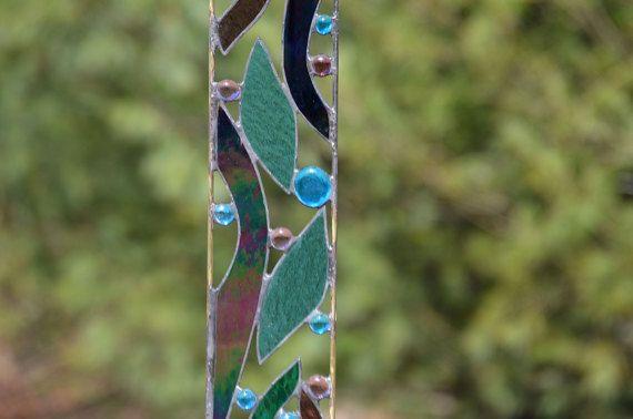 Verrassing! Uw bloemen zijn ontluikende uit voorloopt op de planning. Nu bouwt anticipatie voor het komende seizoen.  Deze tuin sculptuur vangt dat hetzelfde gevoel van anticipatie. Terwijl het hemelsblauw en teal gebrandschilderd glas opvalt, moet je wachten tot de zon drenches het hele stuk om te genieten van de echte schoonheid van Pauwenveren. Schitterende.  Afmetingen: 4 w x 32h, met inbegrip van 7plant  Constructie: Iriserende zwart, sky blue, purple en teal gekleurd glas en Glasstenen…