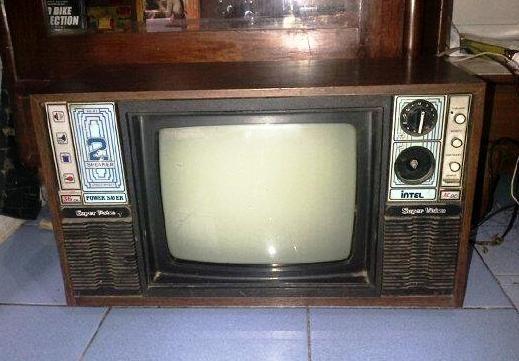 Televisi hitam putih jadul merk Intel. Bodi dari kayu. Masih hidup, tapi gambarnya masih distorsi, mungkin menggunakan antena masa kini, bisa bagus. Sudah ada channel UHF, jadi bisa menangkap channel tv swasta.