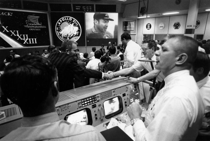 Mission Control in Houston celebrates the safe return of the Apollo 13 crew. Gene Kranz is smoking a celebratory cigar at the right while Deke Slayton, in front of the mission patch, shakes hands.
