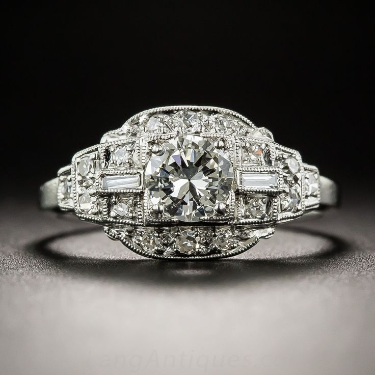 Tastefully tailored geometric architecture distinguishes this original Art Deco dazzler, crisply die-struck and hand-finished in platinum, circa 1930s. The central focus is on a bright white and beautiful transitional round brilliant-cut diamond, weighing .41 carat, accompanied by a GIA Diamond Grading Report stating: I color - VS2 clarity. The scintillating stone is embellished on each side with a straight baguette diamond and small round diamonds set in rising steps, with slender sparkling…
