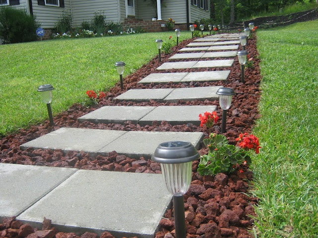 Outdoor walkway with stones, lava rock, solar-powered lights, and geraniums!