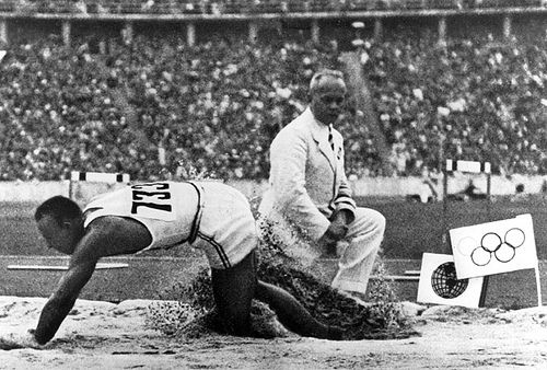 The 1936 Olympics, An Olympic judge watches 'Jesse' Owens land in the broad jump. (photo location: 102-34)