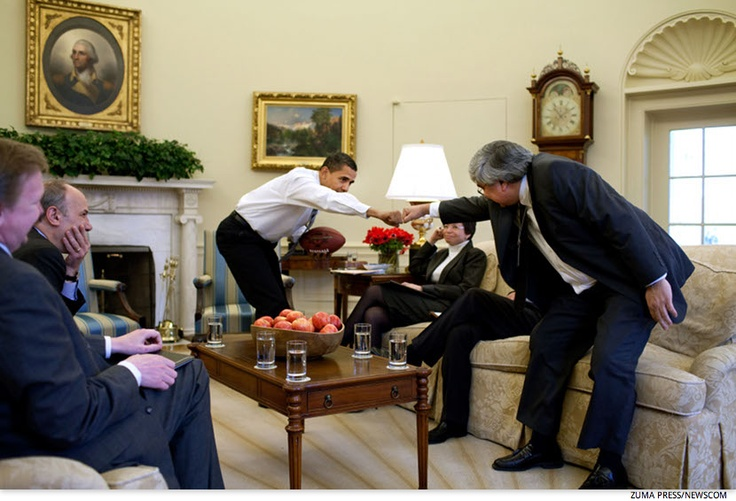 Holding a football, Obama offers a fist-bump to senior staff member Pete Rouse, during a meeting with senior advisors in the Oval Office in April of 2009.