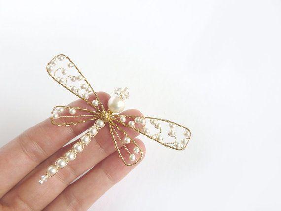 Libélula de perla blanca Esta libélula tiene las siguientes piedras Cuerpo Perla de Swarovski blanco Cola Perlas Swarovski blanco Cristales de Swarovski Ojos Cristal de Swarovski Alas Perlas Swarovski blanco Es macrame con alambre de 14 quilates de oro llenadas. Cada grano se