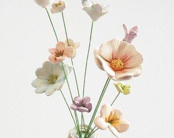 Estas son flores amapolas rojos cerámica preciosas...  Las flores son hechas a mano por mí mismo de arcilla, encendidas en un horno y pintadas a mano con esmalte antes de su segundo disparo. Entonces cuidadosamente colocados y pegados sobre un trozo de cable verde. Se ven bonita como un pequeño ramo en un florero de cuello estrecho... o en masa.   Este listado es para flor 5 tallos... cada longitud del cable es de unos 25-30cm de largo y son todos levemente diferentes en tamaño.. .largest…