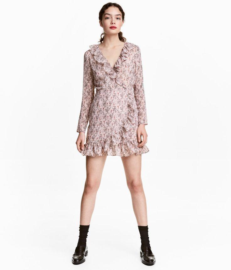 Pudderrosa/Mønstret. Langærmet kjole i tynd, vævet kvalitet med trykt mønster. Kjolen har V-udskæring og er i slå om-facon med flæsekanter foran. Skåret i