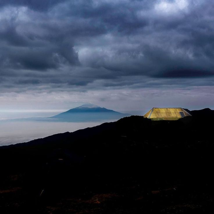 A stormy morning on Mount Kilimanjaro with one lucky person tucked up in bed! That is Mount Meru in the background.  #kilimanjaro #africa #sunset #meru #storm #tanzania #trekking #mountain