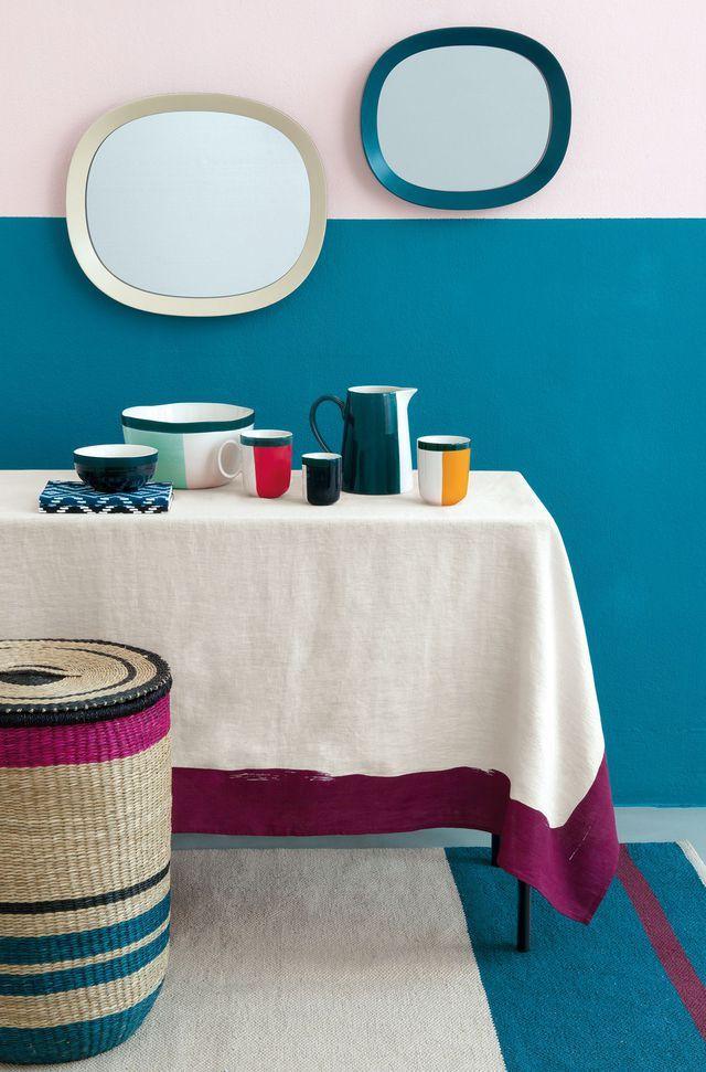Réalisation de Sarah Lavoine avec un grand panier en osier coloré, une nappe blanche et des accessoires pour la table à manger