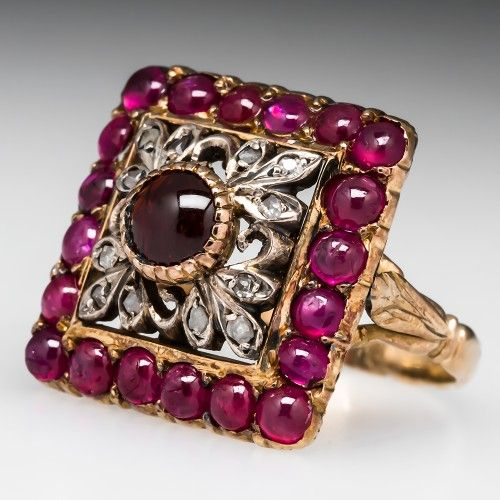 ANTIQUE SPESSERTINE GARNET & RUBY RING W/ FILIGREE DETAILS SILVER & 18K GOLD 1860'S. This stunning antique ring was crafted in the 1860's and is centered with a round cabochon Spessertine garnet set into a silver filigree plaque set with rose cut diamond accents. The center plaque is surrounded by a halo of round cabochon cut natural rubies. The under gallery of the ring is highly detailed with etchings and filigree and the shank is beautifully molded.