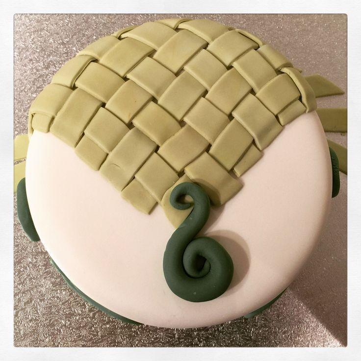 Maori influenced cake with flax type weaving, greenstone pendant and swirls