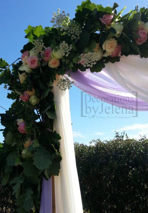 Outdoor Wedding Ceremony arch with fresh flower arrangement and lilac and white drapes - Decorations by Jelena
