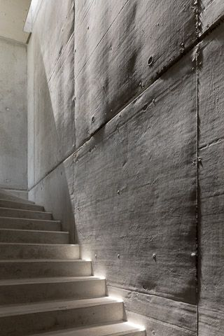 Light bringing to life the beautiful irregular surface of a concrete wall, showing the process of how it was made. Casa da Rainhna by Bruno Erpicum. Photo by Fernando Guerra.