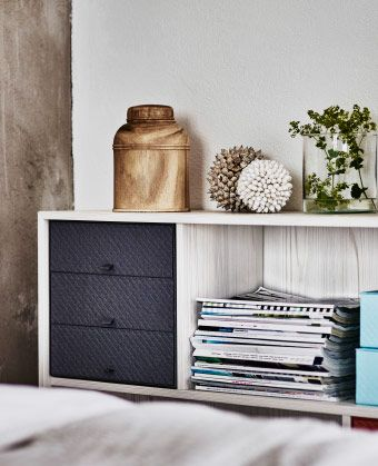 A shelf unit with open compartments in white larch with a mini chest with 3 drawers in dark grey paper board.