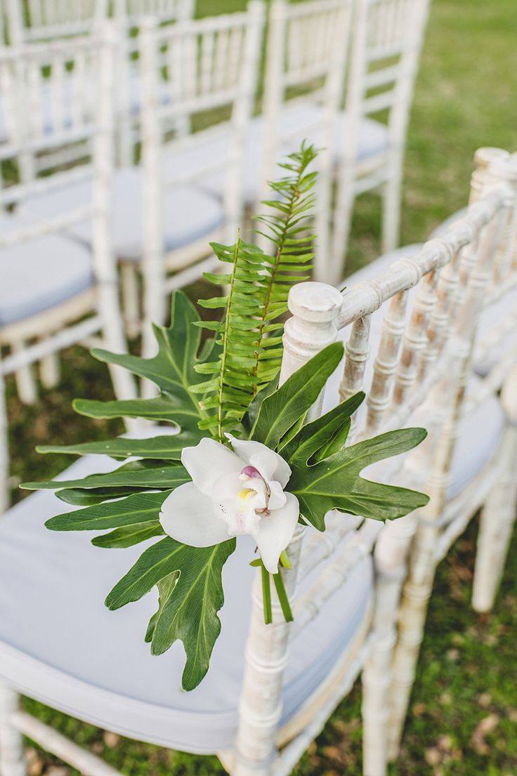 Tropical-themed outdoor wedding aisle chair decor decorated with white phalaenopsis orchids, palm fronds and ferns // Keong Wee and Vicky's Tropical Wedding Beneath a Rain Tree