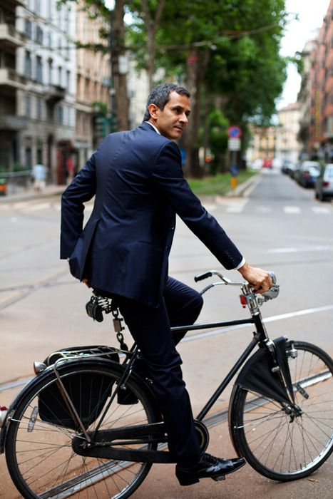 business man. he made the cut. what can i say? he has on a navy suit, gray hair, and is riding a bike.
