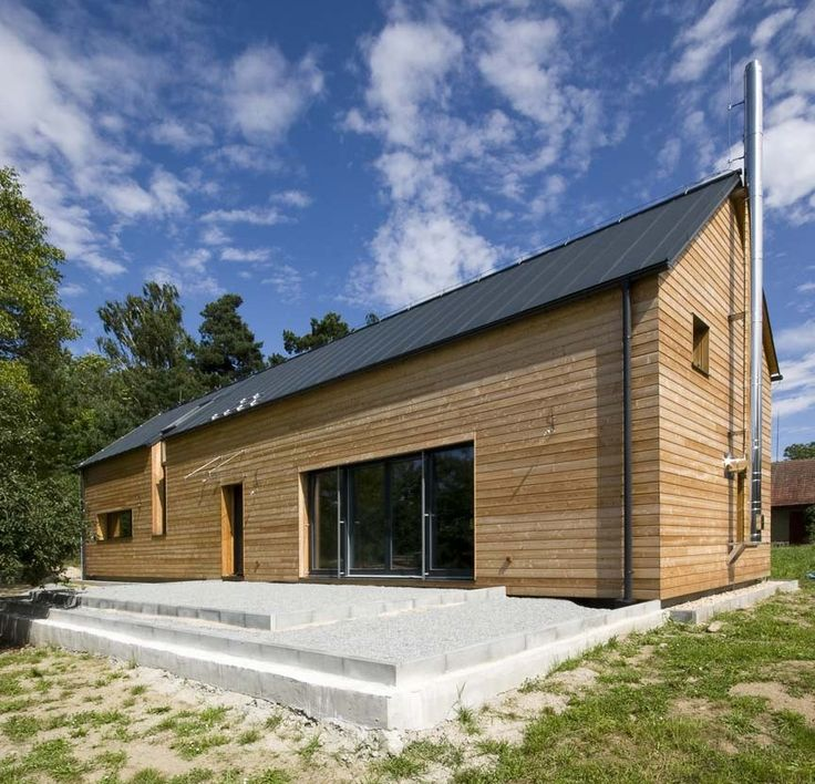 Modern individual wooden house with larch exterior panelling and stainless steel chimney.