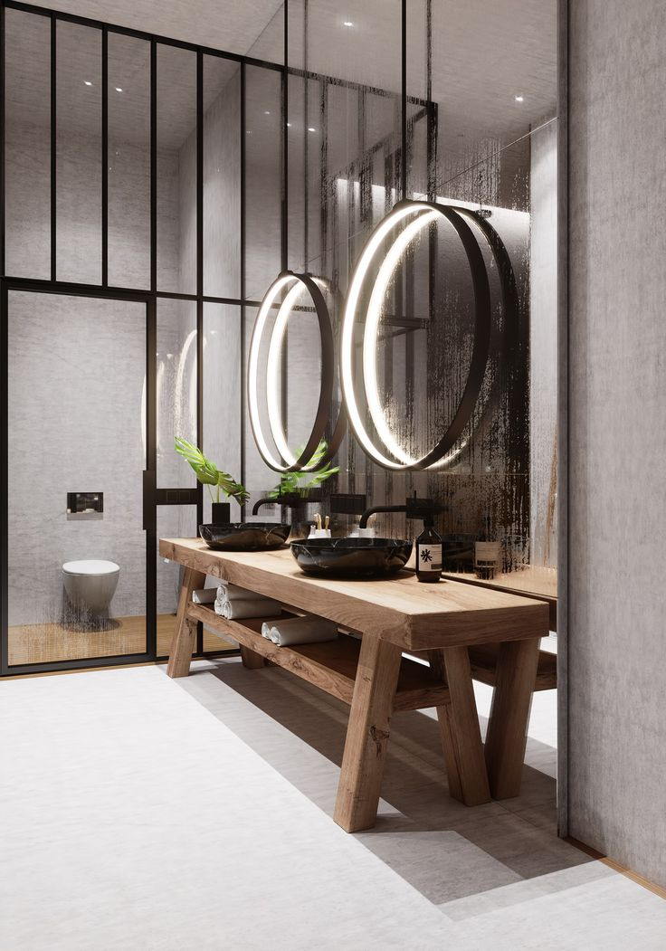 Modern look in this bathroom with these simple rings of light hung on a wall of mirror. Great idea to spiff up standard spec house mirrors.