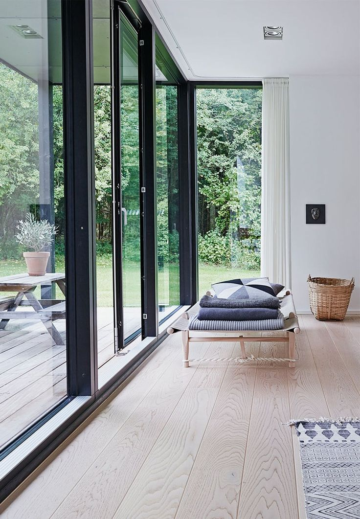 Daybed in light wood in front of the big windows, is a perfect spot for a small break. Its classical design gives a calm look in the room.