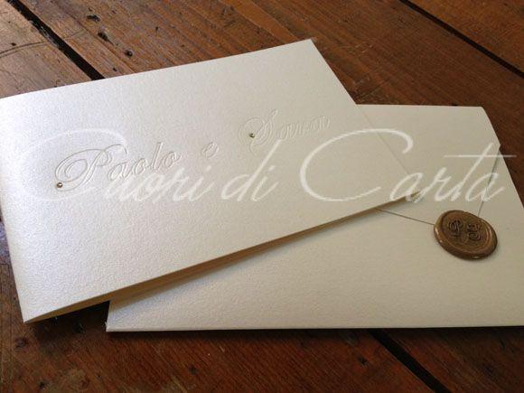 Partecipazione realizzata e scritta a mano, carta perlata avorio, decorata con comi incisi e piccolo brillantino. Completa di busta realizzata a mano, chiusa con sigillo in cera lacca con iniziali sposi.