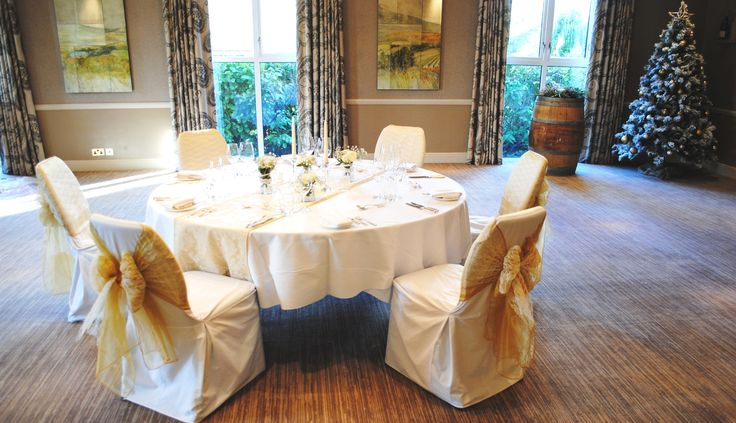 Gold organza sashes on white cotton chair covers at The Vineyard at Stockcross by Simply Bows and Chair Covers