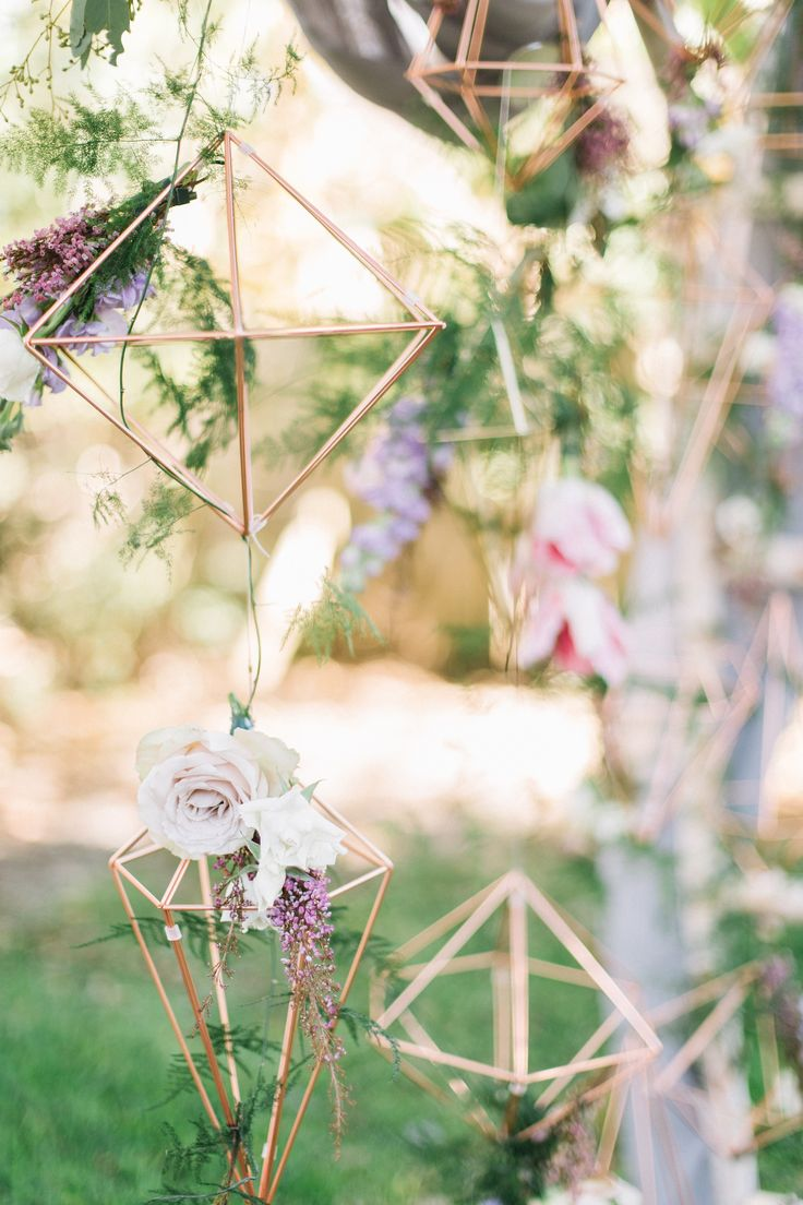 copper himmeli pendants hung from the wedding arbor are dressed with an assortment of lavender and cream roses, heather, purple stock, pink tulips and fern trails.