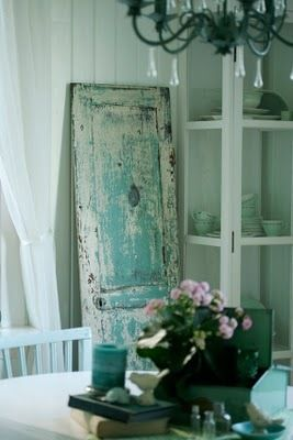 Love this worn aqua door used as a decorative piece in the room....