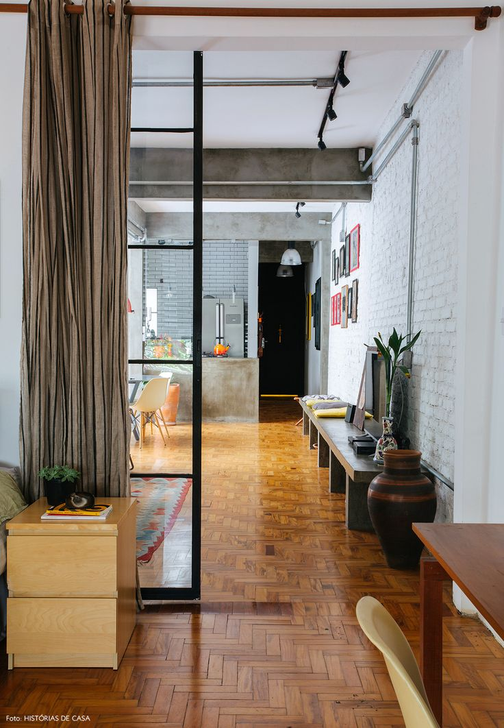 Quarto de casal amplo tem porta de vidro e serralheria para  isolá-lo da área comum da casa.