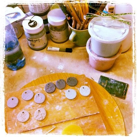 Experimenting with ceramic pendants in the studio for necklaces on leather thongs