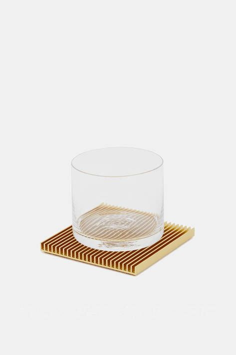 Souda - Gold Fin Set by Designer Shaun Kasperbauer, co-founder of Brooklyn-based Souda, refines a traditional tabletop accessory to its architectural essence with this set of four coasters. The slim, ribbed squares of chromate-conversion-coated aluminum are produced through a unique partnership with a manufacturer of industrial heat sinks. Each cork-backed coaster is the result of a common yet complex manufacturing technique reimagined so as to combine the industrial and the domestic.: