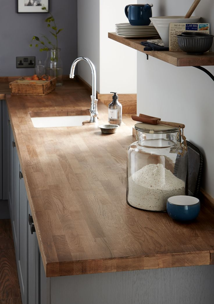A classically inspired swan neck tap and a solid oak block worktop create an elegant and refined look. Fairford Slate Grey Kitchen from The Shaker Collection by Howdens Joinery.