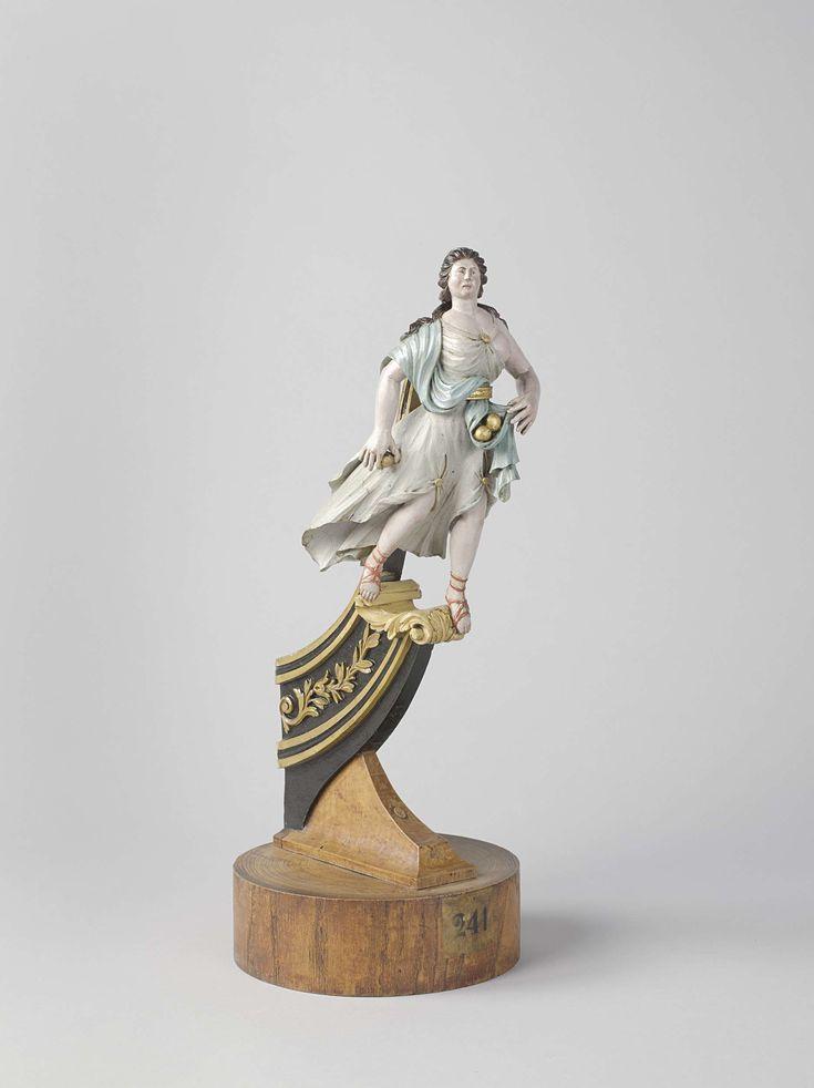 Anonymous | Model of a figurehead, Anonymous, c. 1796 - c. 1800 | Gepolychromeerd model van een staande vrouw op een scheg, op een rond voetstuk. De scheg is versierd met snijwerk van ranken. De vrouw draagt Romeinse kleding en houdt een gouden appel in de rechterhand en twee appels in de plooien van haar sjaal in de linkerhand.