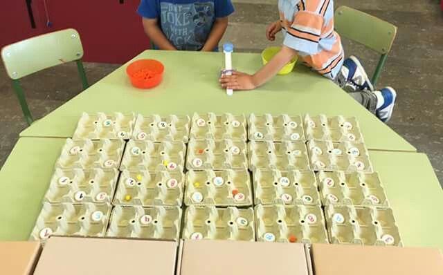 Lanzamiento de minipompón con recuento de puntos. Usamos cajas de huevos, el interior para formar el campo donde ponemos las tapitas con números y las cajas para formar un muro y que el pompón no se vaya muy lejos si no que rebote y caiga en el campo. El lanzador es una madera con un palito que tiene pegado otra tapa de botella, unido todo con un elástico y pegado a la mesa con cinta adhesiva. Dos niños de 3 años tiran alternativamente cada uno su color, dicen el número si cae en alguno y al…