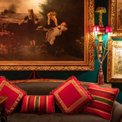 Former Neiman Marcus fashion exec and fanatical antiques collector Derrill Osborn, at home in his Dallas apartment, where red and green reign supreme; Pictured is antique oil paintings and red pillows; Photography by Wynn Myers